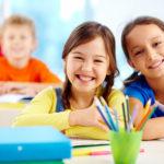 Photo of 3 children with school supplies