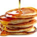 Photo of syrup dribbling down a stack of pancakes
